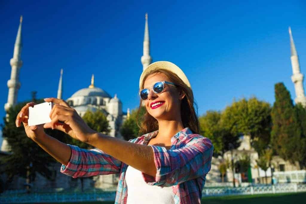 Estambul - Girl in the hat making selfie by the smartphone on the backgroun