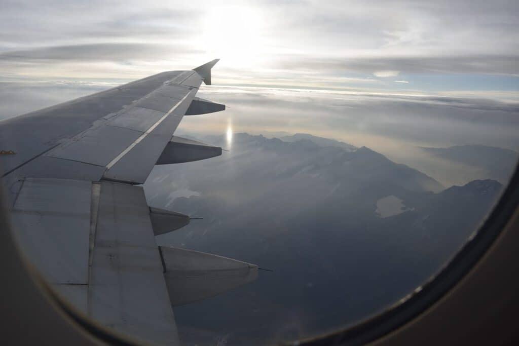 Canva Avión vuelo viaje viajar ala de avión paisaje aéreo volar viajando vacaciones vuelo a Suiza sobrevolar descansar pensar en las nubes cielo nubes 1200x800 - Su destino ideal de viaje.
