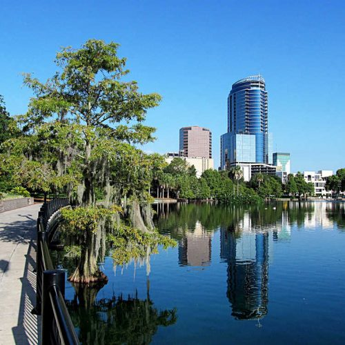 View of Downtown Orlando from across Lake Eola Park in an earl summer day in this city located in Central Florida. Orlando is known worldwide for being the location of some of the most famous theme parks in the world