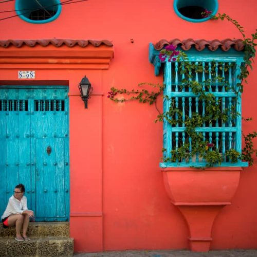 The classic city of Cartagena is full of colonial Spanish architecture, which lives on today in modern Colombian society.  A caucasian woman sits on the steps to the house.