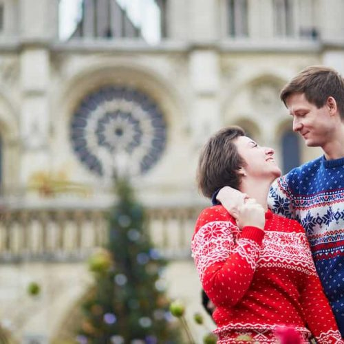 Happy couple in colorful sweaters on a street of Paris decorated for Christmas, near Notre-Dame cathedral
