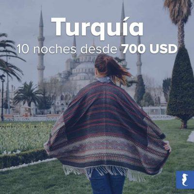 Turquía - Mujer Joven Caminando Por Un Jardín Con Un Impresionante Palacio Turco De Fondo